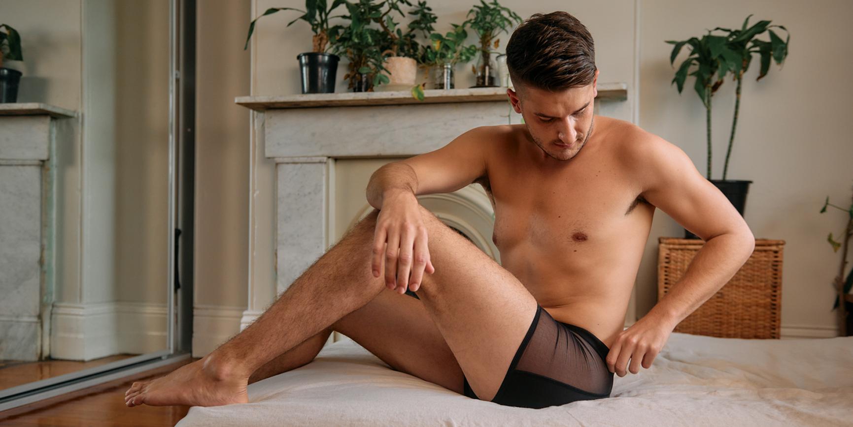 Man sitting on bed wearing lingerie for men